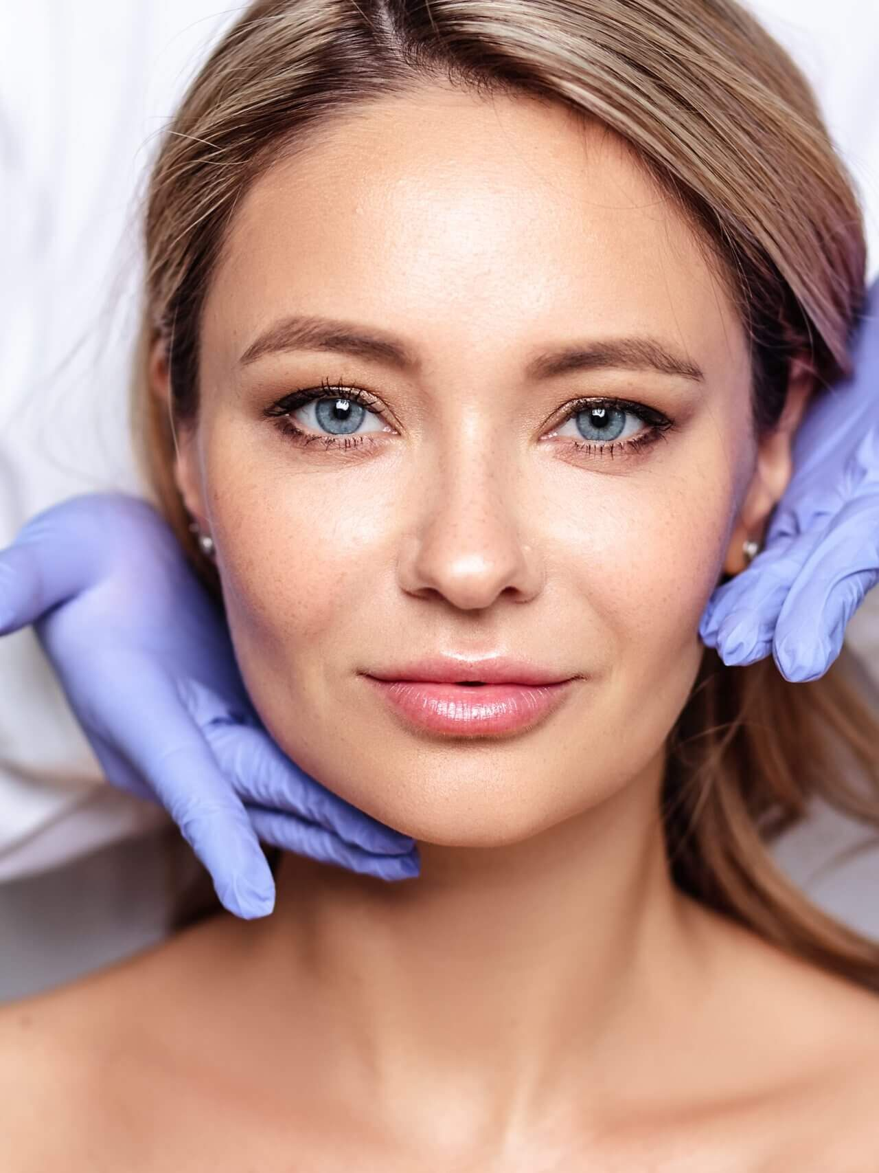 Close up portrait of young blonde woman with cosmetologyst hands in a gloves. Preparation for operation or procedure. Perfect skin, spa and care